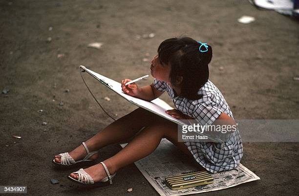 A young Japanese girl sits on the ground absorbed in her drawing