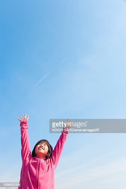 A Young Japanese Girl Smiling and Raising her Arms Towards the Sky