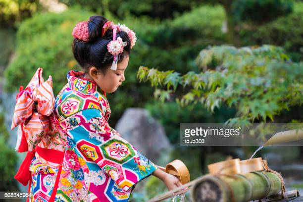 A young Japanese girl wearing a traditional kimono ceremoniously washing her hands