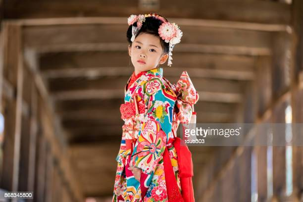 a young japanese girl wearing a traditional kimono while celebrating her shichi go san - obi sash stock pictures, royalty-free photos & images