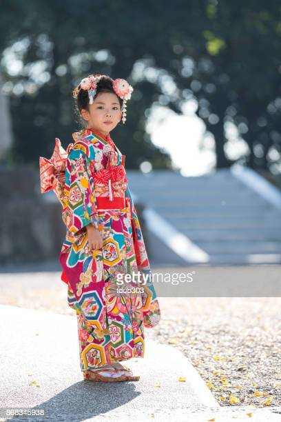 a young japanese girl wearing a traditional kimono while celebrating her shichi go san - traditional clothing stock pictures, royalty-free photos & images