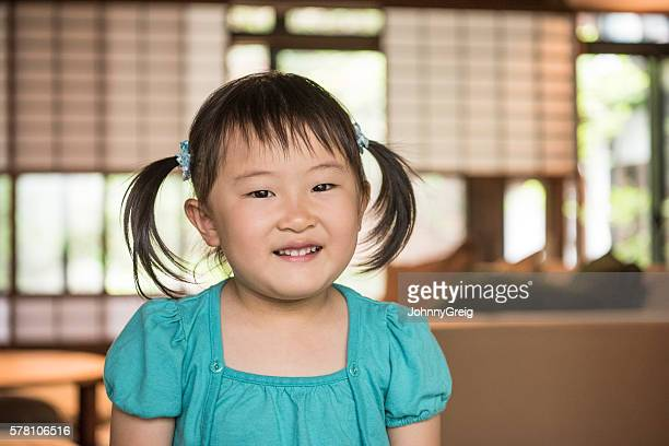 Young Japanese girl with pigtails looking at camera, portrait