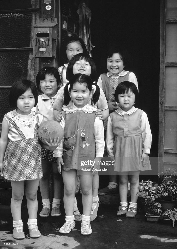 Young Japanese girls pose for a photograph in front of a home in Tokyo, Japan.