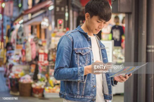 Young japanese man and asian friend looking for travel location  using mobile phone and spending time together in japan