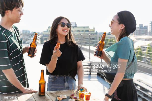 young japanese man and two women standing on a rooftop in an urban setting, drinking beer. - ビール瓶 ストックフォトと画像