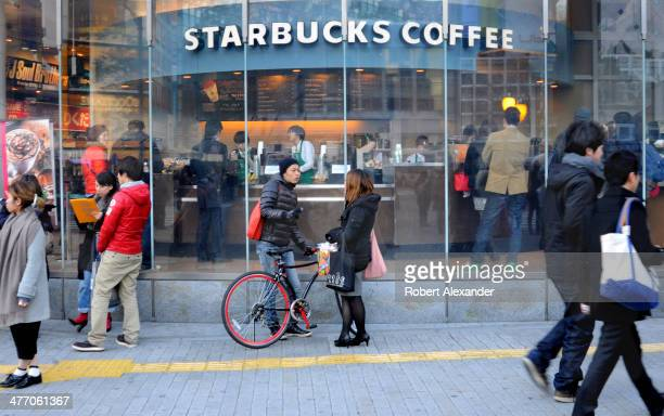 A young Japanese man and woman talk in front of a Starbucks Coffee shop in Tokyo's trendy Shibuya district
