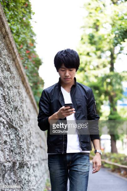 Young Japanese man confidently walking down the street as he uses his smart phone