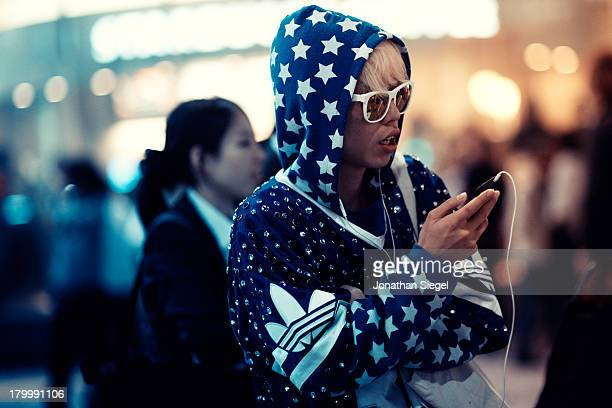 Young Japanese man dressed in crazy and stylish fashion, listens to music on his mobile phone at night. He is standing near busy Shibuya crossing.