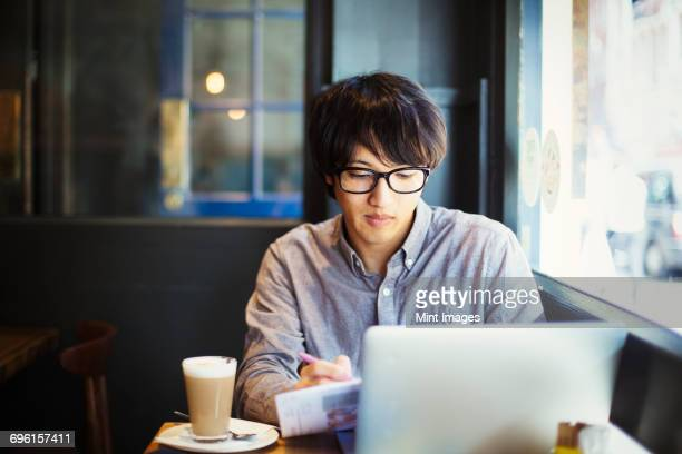 Young Japanese man enjoying a day out in London, sitting in a cafe, using laptop computer.