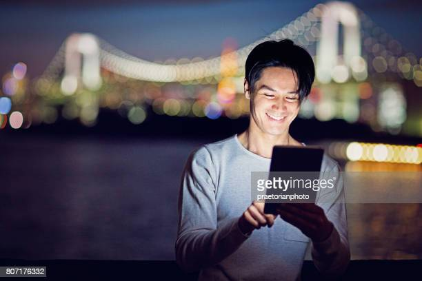 Young Japanese man is browsing with his tablet at the front of Tokyo city and Rainbow bridge.