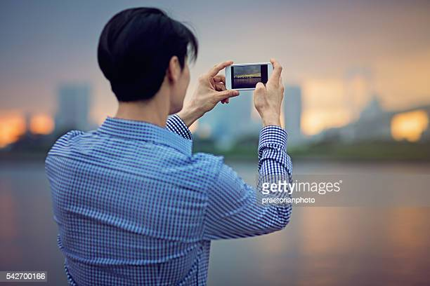 young japanese man is  taking photo - capturing an image stock pictures, royalty-free photos & images
