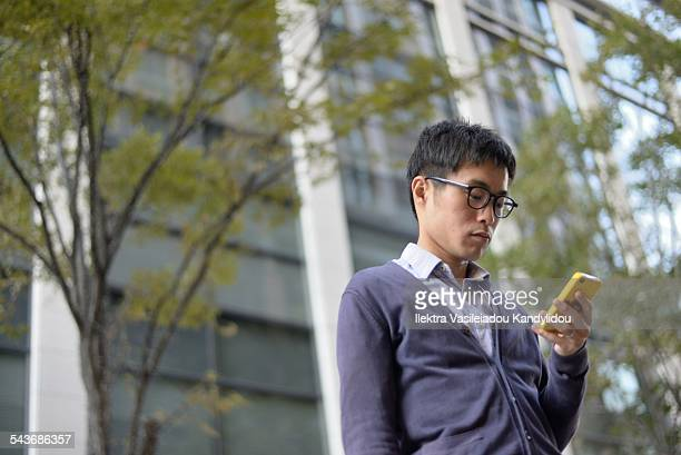 Young Japanese man standing outside, texting.
