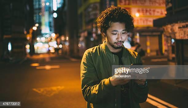 Jeune homme japonais à envoyer des SMS sur le téléphone
