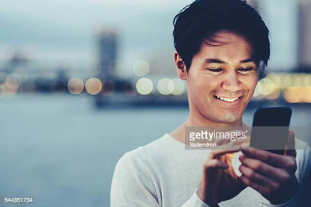 Jungen japanischen Mann SMS auf das Telefon