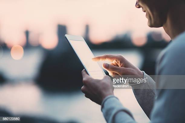 Young japanese man texting on the tablet