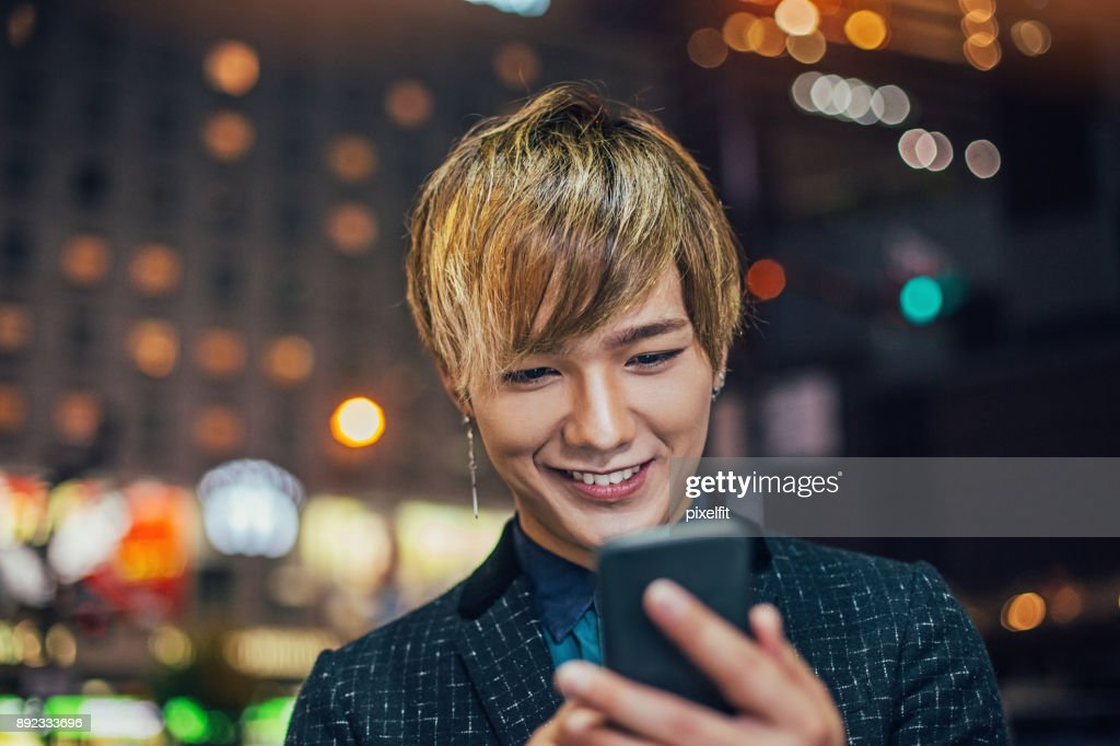 Young Japanese man texting outdoors at night