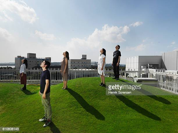 5 young japanese people looking up