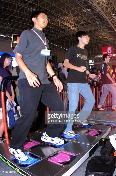 Young Japanese perform steps to a hiphop dance on the electric arcade game machine called Konami's Dance Revolution which guides dancers' steps with...