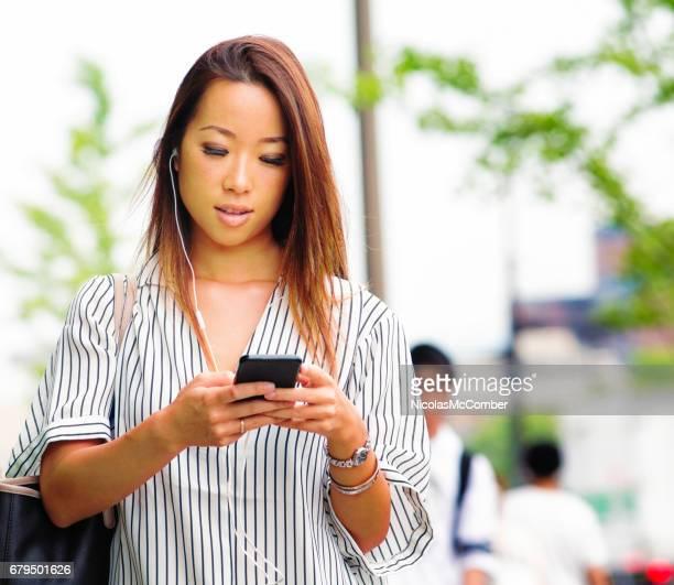携帯電話でポッド キャストを選択する若い日本人女性