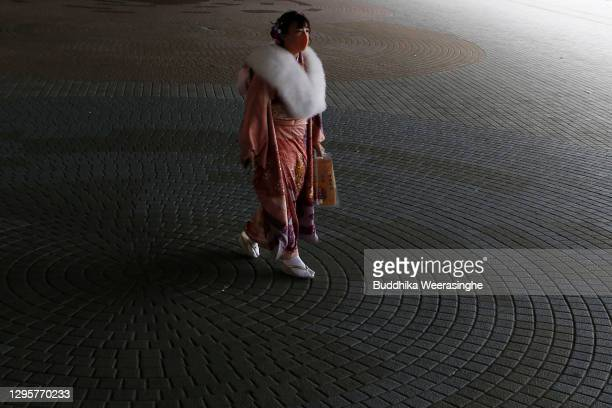 Young Japanese woman dressed in traditional kimono and wearing a face mask leaves after she attended a Coming-of- Age ceremony at Koshien national...