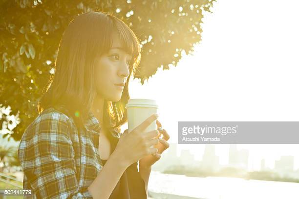 Young Japanese woman drinking coffee on beach