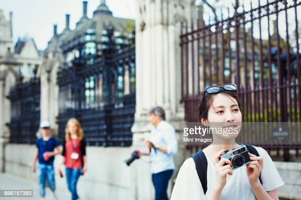 Young Japanese woman enjoying a day out in London, holing a camera.