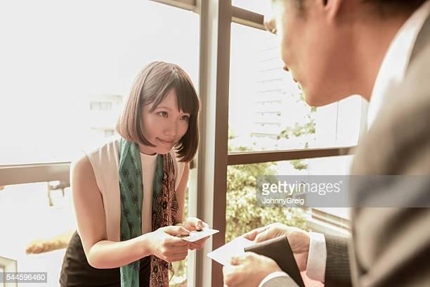 giovane donna giapponese consegnare biglietto da visita al collega - biglietto da visita foto e immagini stock