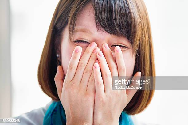 Young Japanese woman hiding her face while laughing.