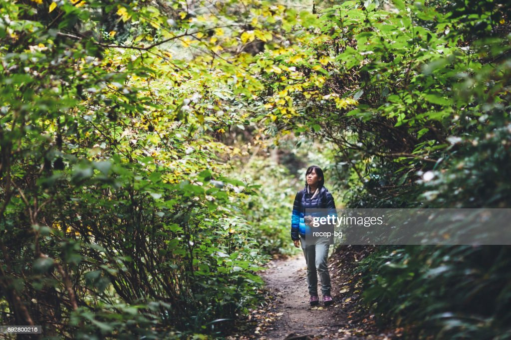 A young Japanese woman is hiking in a mountain.