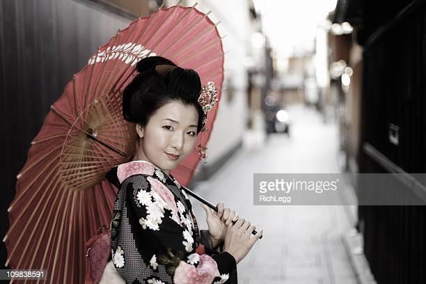 Mujer joven en un quimono japonés con sombrilla