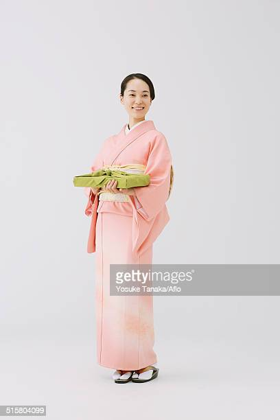 Young Japanese woman in a traditional kimono against white background