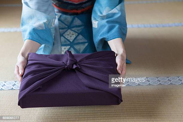 Young Japanese woman in kimono giving parcel