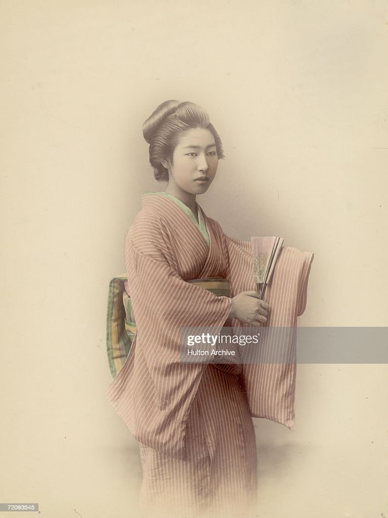 A young Japanese woman in traditional kimono and obi and carrying a fan, circa 1880.