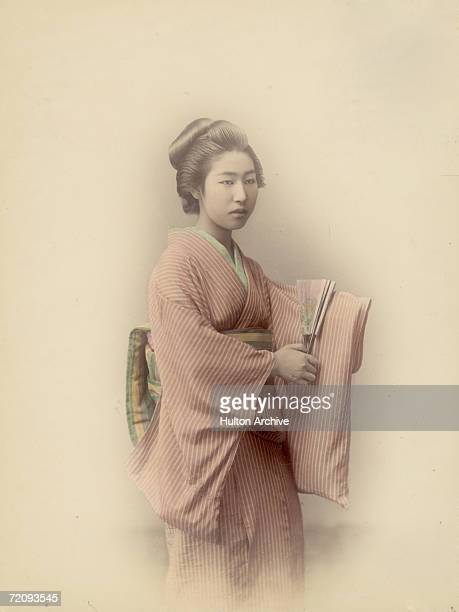 A young Japanese woman in traditional kimono and obi and carrying a fan circa 1880