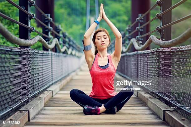 joven japonesa está haciendo yoga en el puente de cuerda en el bosque - filosofía fotografías e imágenes de stock