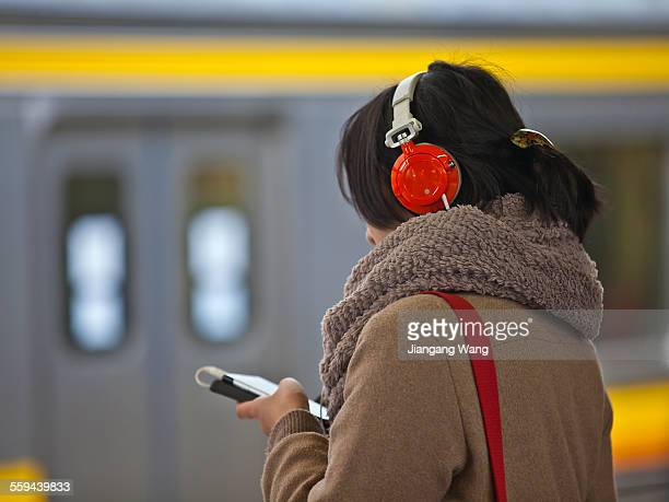 Kawasaki Kanagawa Prefecture Japan March 8 2015 A young Japanese woman is listening music with her mobile phone at a railway station
