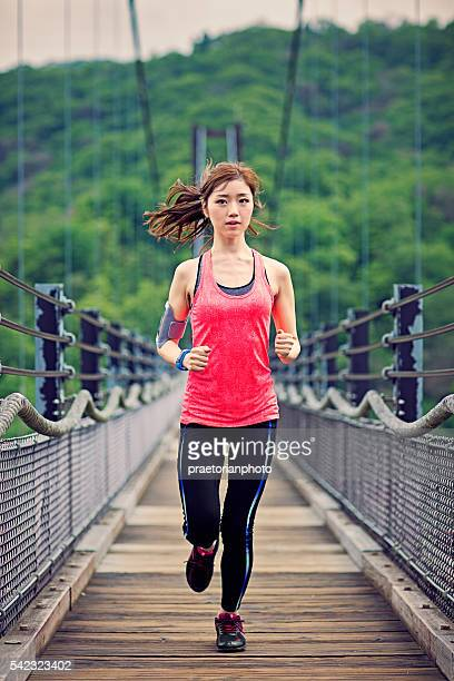 Young Japanese woman is running on the rope bridge