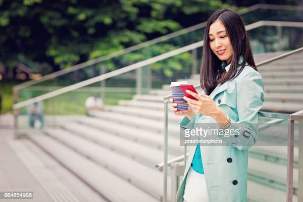 Young Japanese woman is texting with her mobile phone