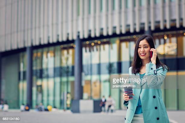 Young japanese woman is walking in the city and talking using her mobile phone