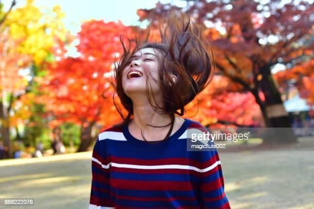 東京公園で彼女の長い髪と遊ぶ若い日本女性