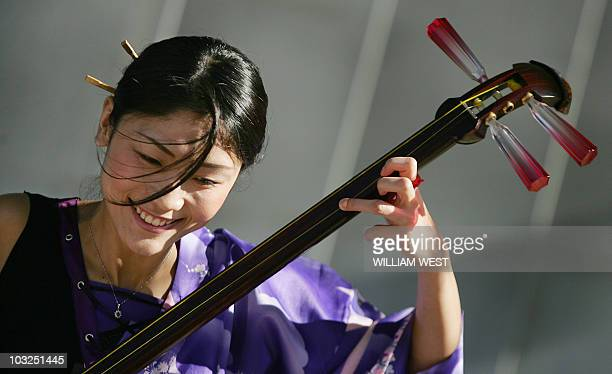 A young Japanese woman plays a traditional guitar at a Japanese People for Peace vigil to remember the 60th anniversary of the atomic bomb been...