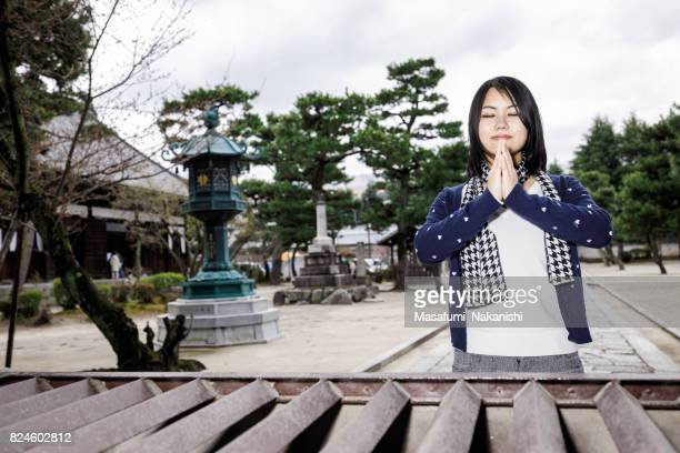Young Japanese woman praying at a Japanese temple