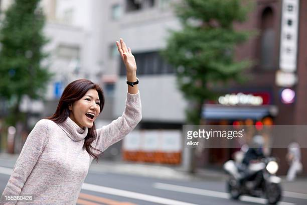 Young Japanese woman raising hand to catch taxi in Tokyo