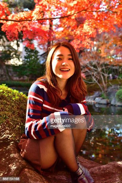 young japanese woman relaxing under bright autumn leaves, tokyo - suginami stock photos and pictures