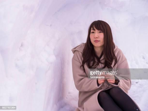 雪の洞窟で座っている日本の若い女性。