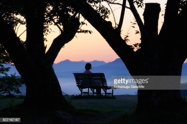 Young Japanese woman sitting on a bench in the countryside