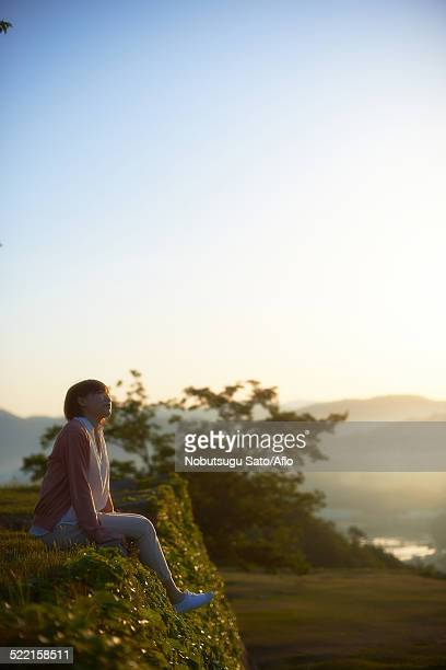 Young Japanese woman sitting on grass in the countryside