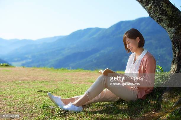 young japanese woman sitting with book in the countryside - チノパンツ ストックフォトと画像