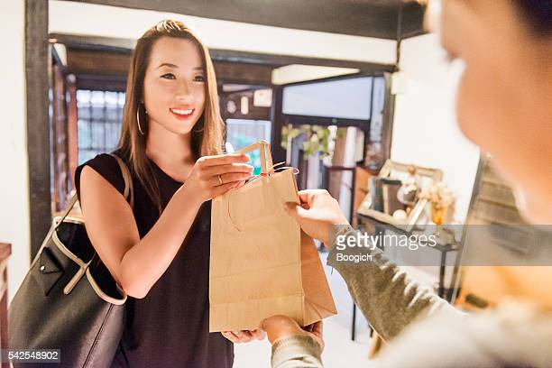 Young Japanese Woman Smiles As She Finishes Shopping Transaction