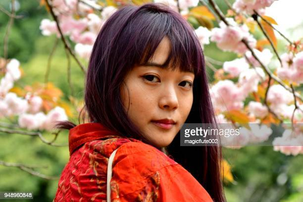 young japanese woman standing against cherry blossom in suburbs of tokyo - hanami stock pictures, royalty-free photos & images